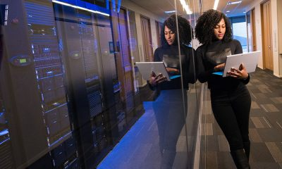 Woman leaning on a glass wall separating her from wall of data servers managed by AI.