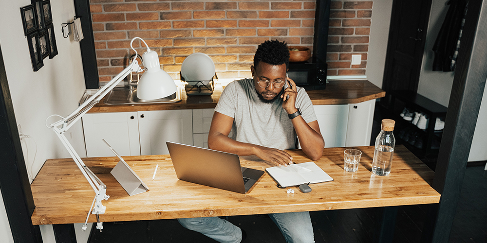 Man working from home displays work-life balance at his desk, leaning into a phone call.
