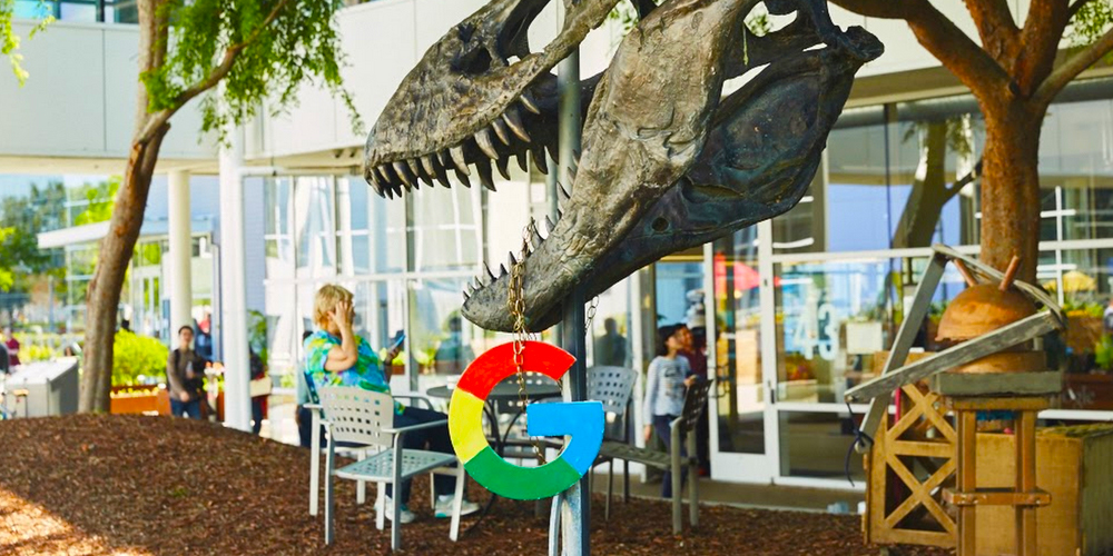 Dino holding Google logo on campus.