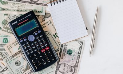 Calculator sitting on top of 20 US dollars ready for income verification.