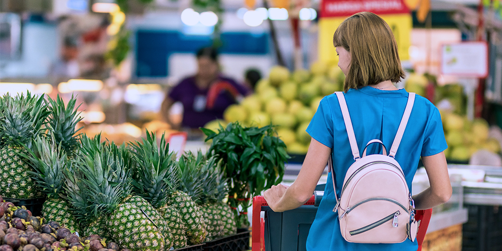 Woman grocery shopping, showing economy changes