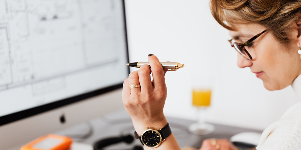 Woman holding a pen working on risk management plan.