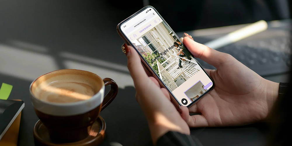 Casa Blanca app looking for dream home on smartphone in female hands at table.