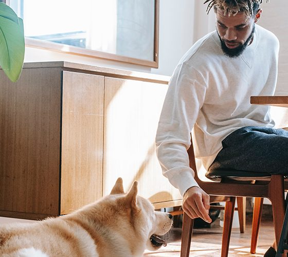 Man sitting in a home with dog at his feet, subject to housing discrimination.