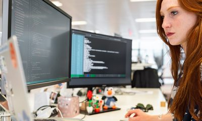 Woman working at desk with multiple desktops open to AI tools.