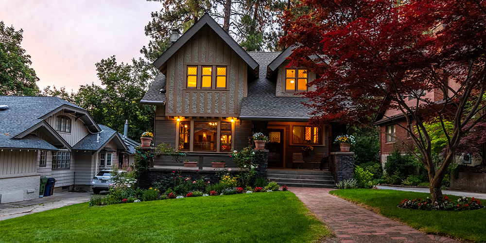 A house at dusk with lights illuminated, favored by housing market.