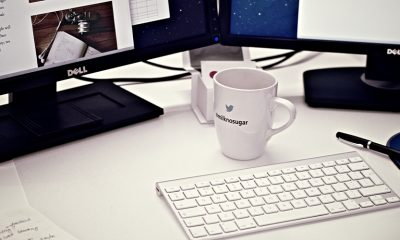A desk with a blogging website open on the computer and coffee cup in front.