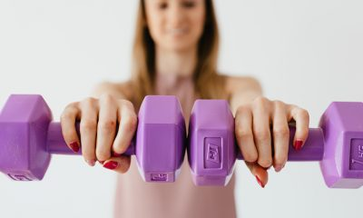 Fitness woman holding purple dumbbells