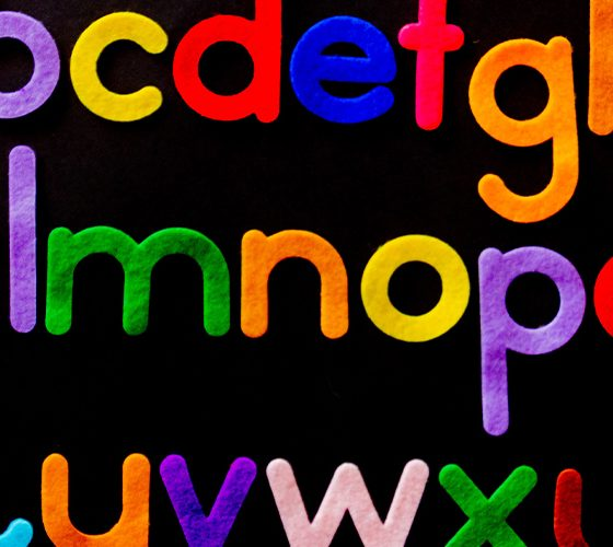 Bright colored alphabet on dark background, a starting place for branding and naming a company.