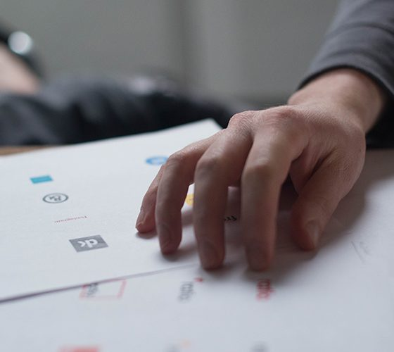 Logo design sketches being drawn on paper and hands pointing to various designs.