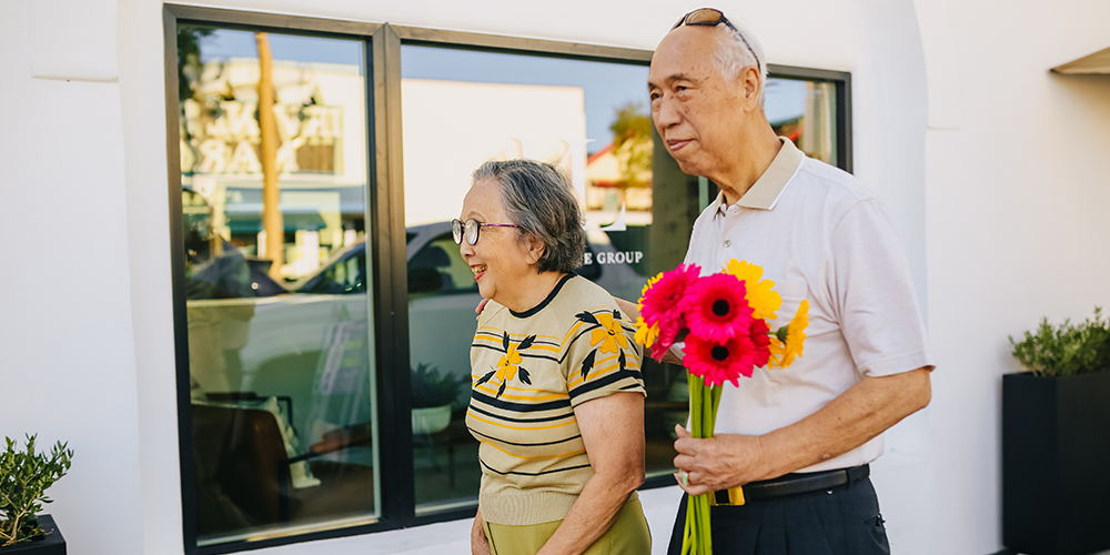 Senior real estate with two senior citizens walking around outsides holding flowers.
