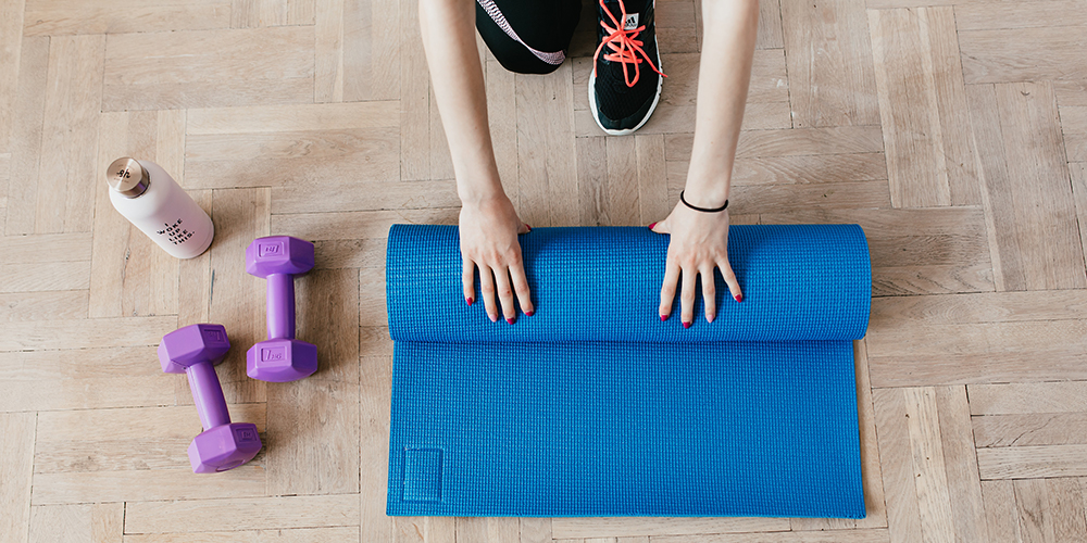 Woman rolling up yoga mat with dumbells next to it in her home gym setup.