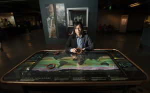 Interactive Visualization Exhibit with person seated behind it, showing moving mountains beneath their hands.