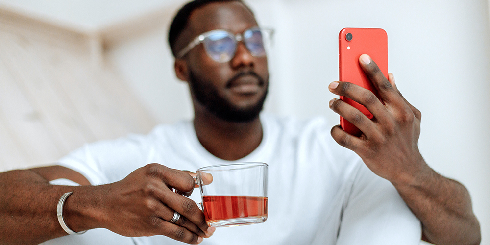 Man holding half-empty mug in one hand and phone open to Clubhouse for entrepreneurs..