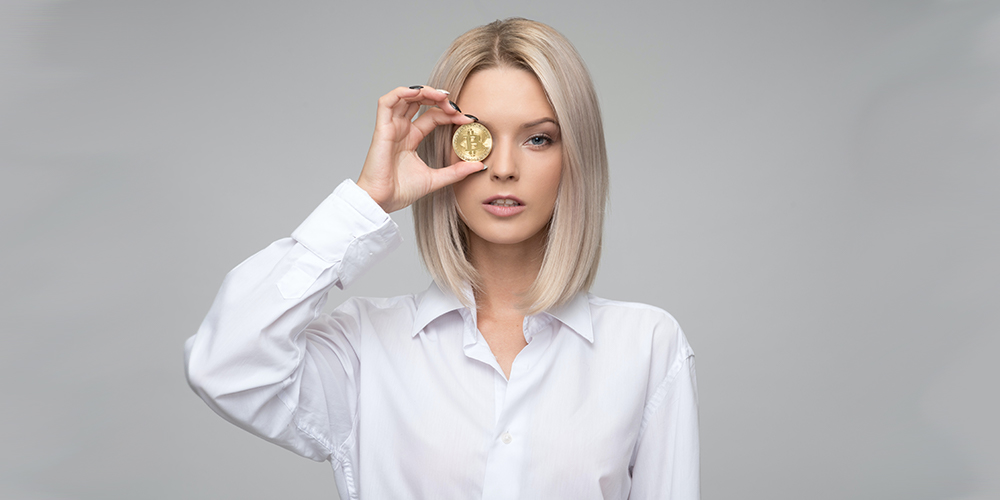 Woman holding Bitcoin up to her eye, standing against gray backdrop.