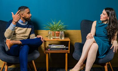 A Black man on the left and a white woman on the right deep in conversation in a blue and yellow room.
