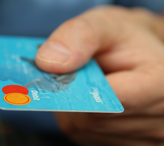 Credit card being held out to our point of view, part of a buy now pay later system.