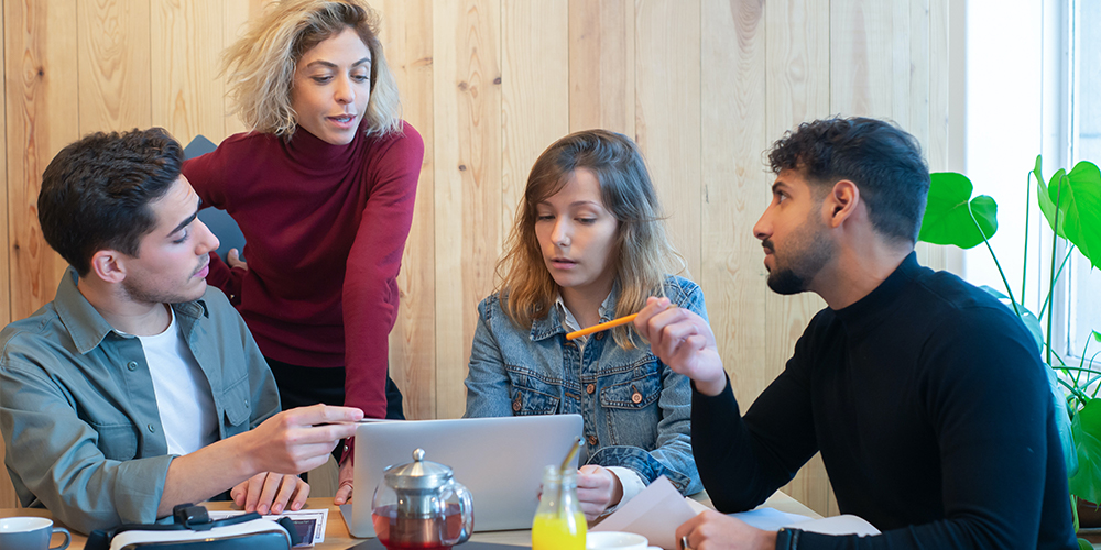Freelancers and entrepreneurs working together in a meeting room, two men and two women, discussing over a laptop.