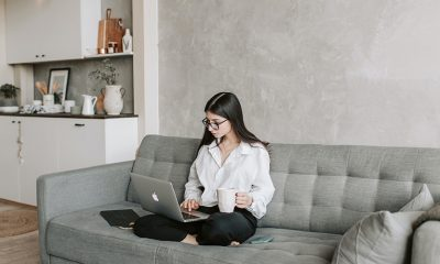 Woman seated on gray couch in gray living room using digital housing market resources on laptop.