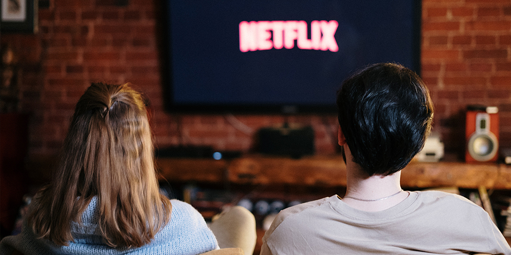 Two people watching Netflix on a TV while seated on a couch.