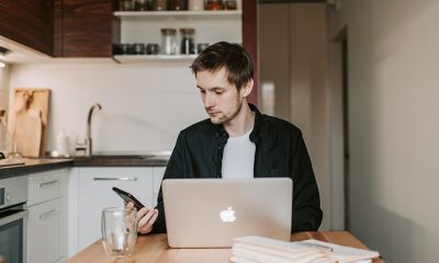 Man seated at kitchen table with laptop and checking phone, searching to avoid real estate scams.