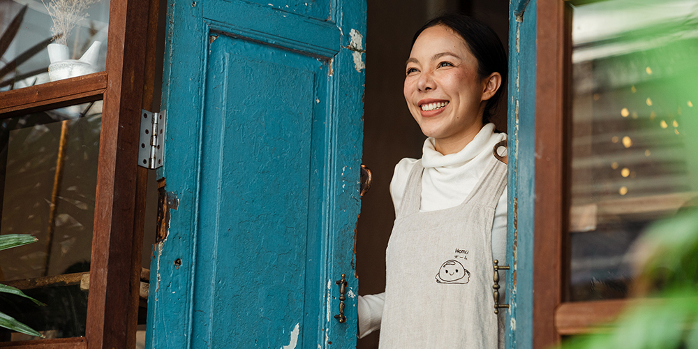 Woman standing in blue doorway welcoming people into their small businesses. Support for small businesses