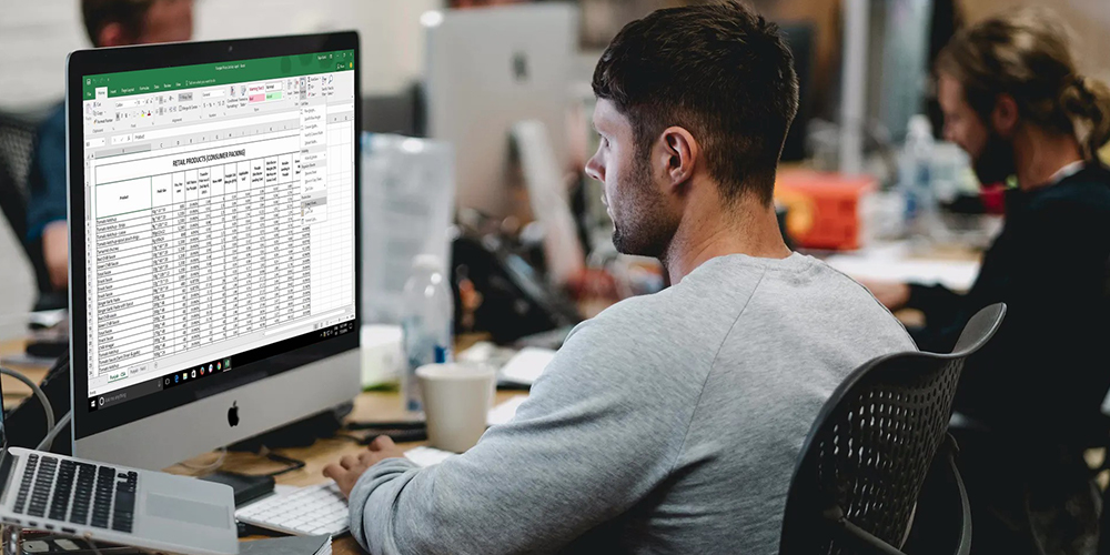 Spreadsheets open on desktop with man in office setting.