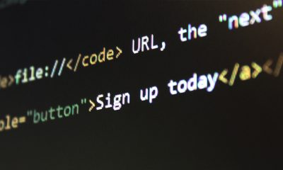 Picture of a screen with HTML code written on it, showing the title tag and a sign up button.