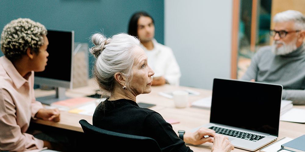 A diverse range of employees sit at a table, with learning about how to avoid age discrimination.