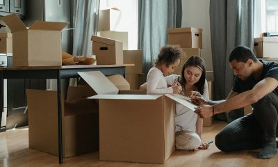 Family unloading boxes inside of a home, previous home buyers.