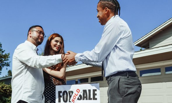 Real estate agent shaking hands with couple over a For Sale sign marked sold from Zillow
