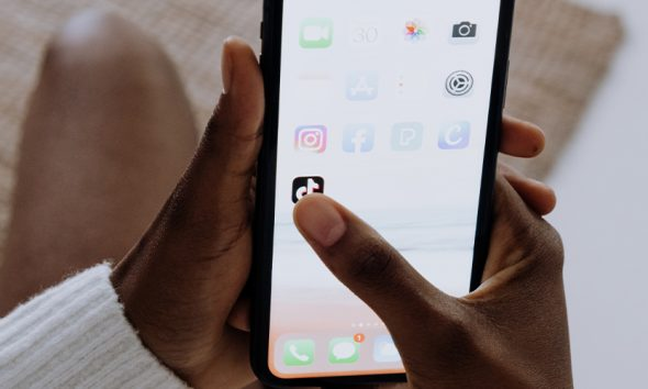 Hands holding a phone about to open the TikTok app