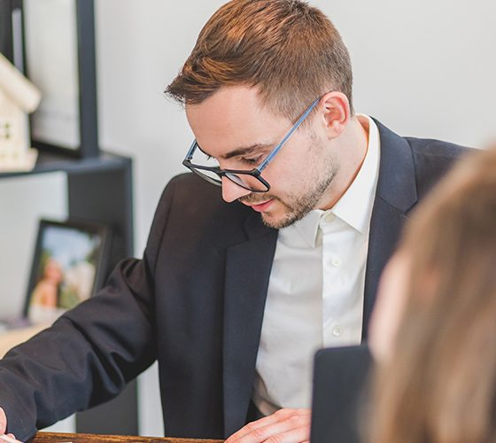 Man reviewing paperwork from Zillow listing with couple looking to buy