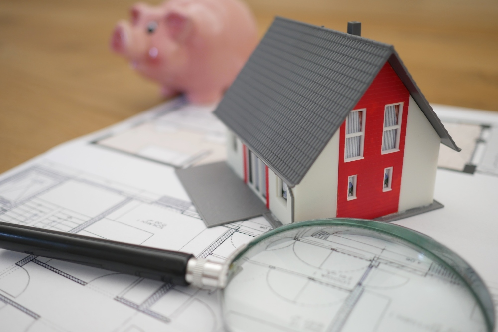 Magnifying glass and toy house representing searching for a home with a piggy bank in the back.