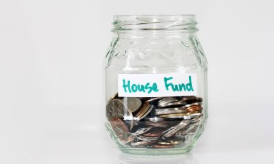 Glass jar of coins labeled House Fund.