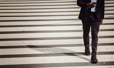 Man walking on crosswalk with phone, but his private data could be vulnerable.
