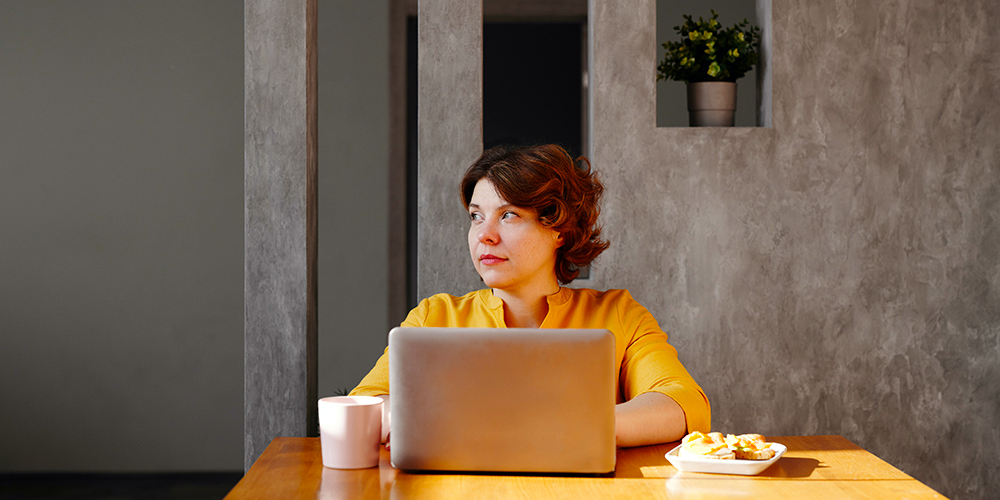 Woman at computer, looking away from remote work.