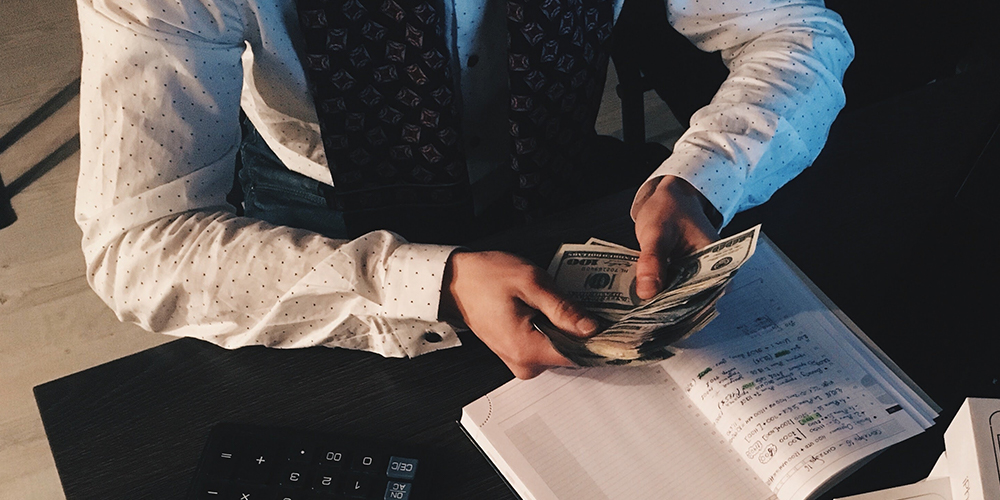 Billionaires counting money at desk in journal
