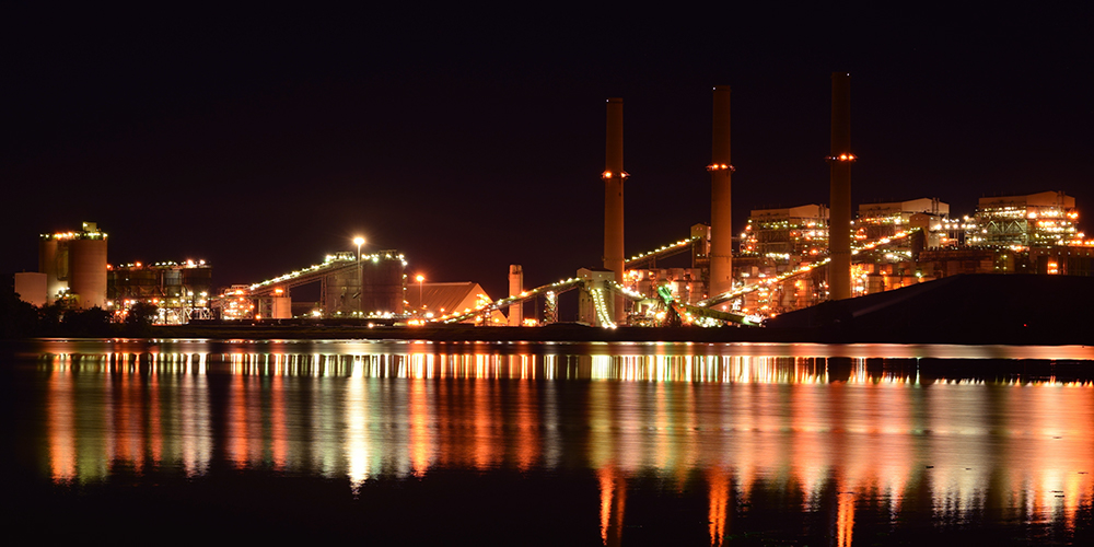 Manufacturing plant at night across the water with orange and red reflections.