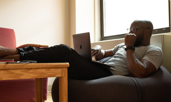 Man reclining on beanbag with laptop, thoughtful. Considering tactics before you quit your job.