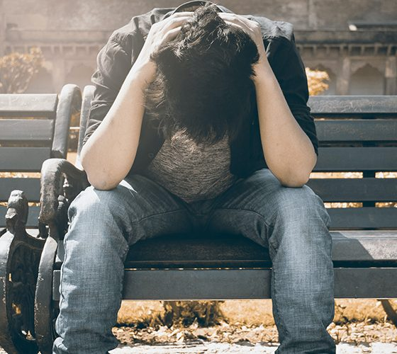 Upset young man seated on bench with head in hands thinking about money.