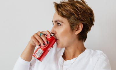 Woman drinking Coca Cola against plain wall