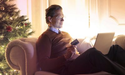Man on laptop open to Twitter, considering his holiday shopping with Christmas tree behind him.