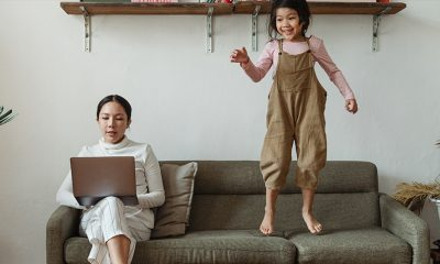 Mother working remotely with a child jumping on the couch next to her working.