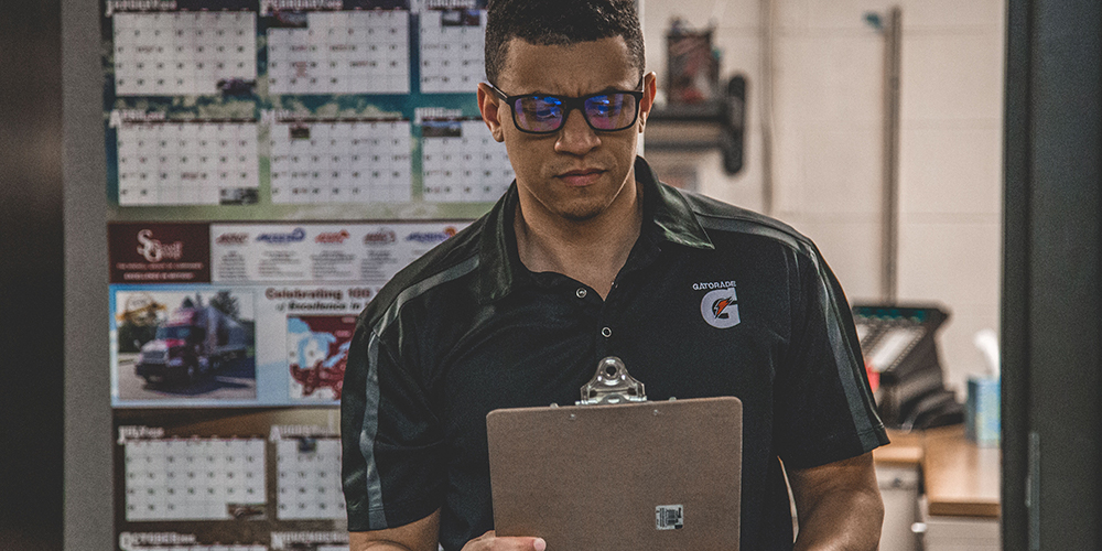 A serious man considers a clipboard in potential employment scams.