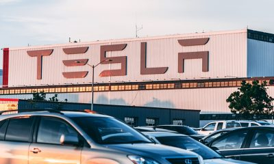 Tesla factory at sunset, with cars parked outside the building.