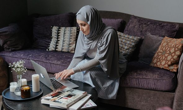 Woman in hijab sitting on couch, working from home on a laptop