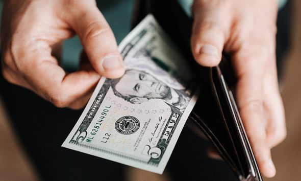 Wallet open with $5 bill out, reflecting spending habits