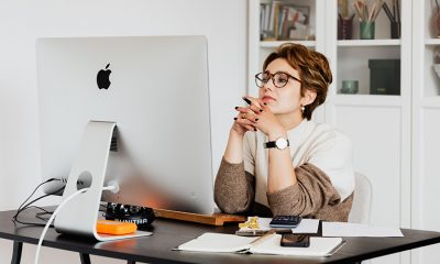 Woman sitting at computer with fingers steepled, awaiting a rejection email or any response from HR at all.