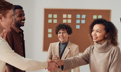 A meeting room with people shaking hands over acquiring a business